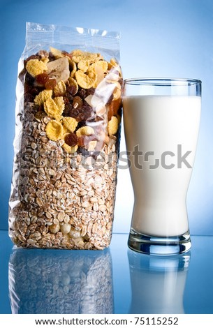 Fresh Glass of Milk and Closed Pack of muesli on a blue background - stock photo