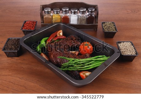fresh glazed baked big beef meat rib chunk under sweet sauce with tomatoes hot chili pepper asparagus different peppercorn spices in black deep tray on light walnut wooden table - stock photo