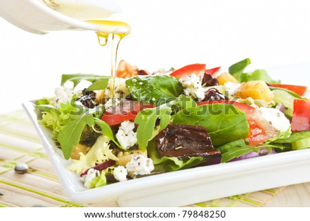 Fresh goat cheese salad with fresh vegetables and olive oil. - stock photo