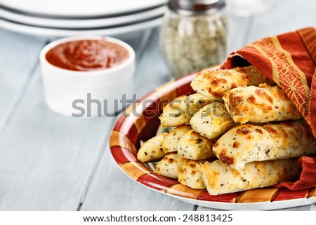 Fresh golden, cheesy breadsticks with marinara sauce and parmesan cheese in background. Shallow depth of field. - stock photo