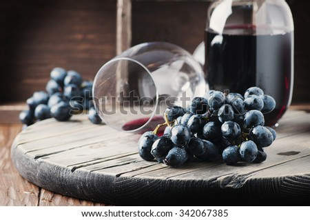 Fresh grape and red wine on the vintage table, selective focus - stock photo