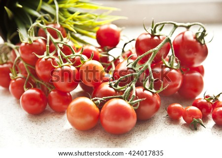 Fresh grape tomatoes for use as cooking ingredients with a halved tomato in the foreground with copyspace - stock photo