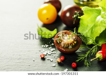 Fresh grape tomatoes with salade leaves and salt for use as cooking ingredients with a halved tomato in the foreground with copyspace  - stock photo