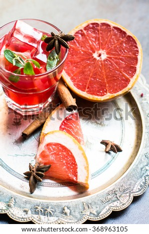 Fresh grapefruit cocktail with cinnamon and anise star spices on rustic background - stock photo
