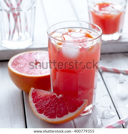 Fresh grapefruit juice with fruits and crushed ice in glasses, selective focus - stock photo