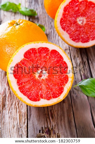 Fresh grapefruit with slices on a wooden table. Wooden background.