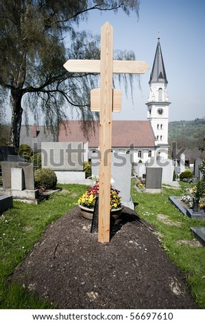 Fresh Grave with Church in Background, taken in Austria - stock photo