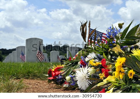 Fresh grave with flowers at the Arlington National Cemetery in Arlington, Virginia, near Washington DC. Low-angle view from the ground up. - stock photo