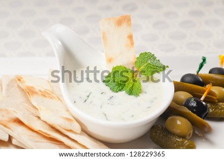 fresh Greek Tzatziki yogurt dip and pita bread and pickels - stock photo