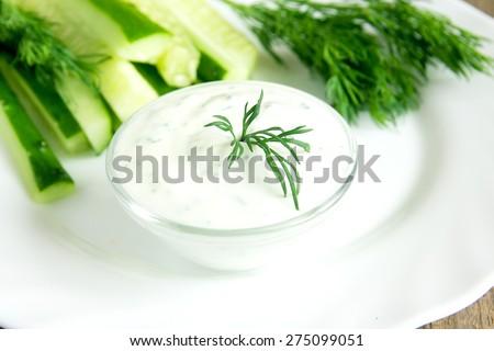 fresh Greek Tzatziki yogurt dip (sauce) and some ingredients (vegetables) on white plate, horizontal close up - stock photo