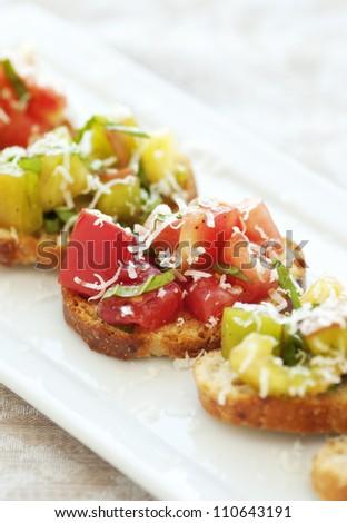 Fresh green and red heirloom tomato bruschetta - stock photo