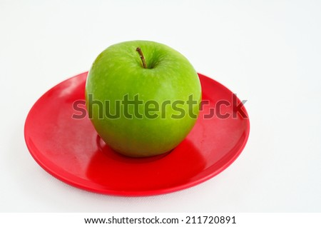 Fresh green apple on red plate for Rosh Hashanah Jewish holiday, on white background with copy space - stock photo
