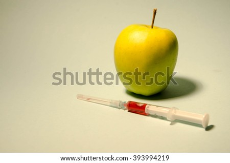 Fresh green apple with a syringe inject  - stock photo