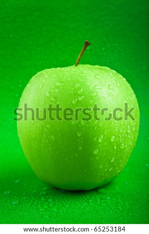 fresh green apple with drops of water - stock photo