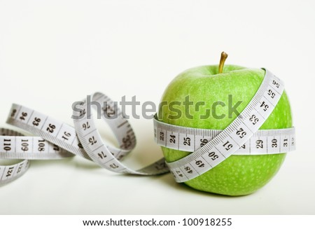 Fresh green apple with measuring tape on white background