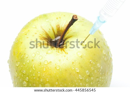 Fresh green apple with water drops and syringe injection isolated on white background - concept for genetically modified foods for diet and future health concept. - stock photo