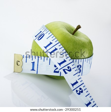 Fresh green apple wrapped in a measuring tape - stock photo