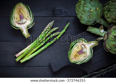 Fresh green artichokes  and asparagus on wooden cutting board, selective focus - stock photo