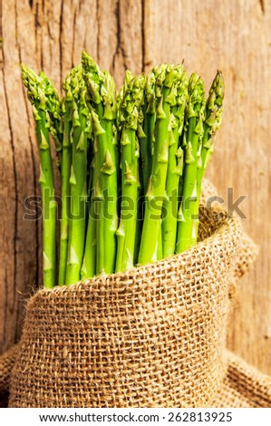 Fresh Green Asparagus Harvest in Vintage Burlap Bag on Wood Table Background, Concept and Idea of Food Cook Rustic Still life Style. - stock photo