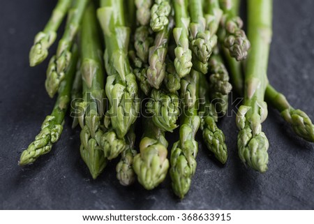 Fresh green asparagus on a green board - stock photo
