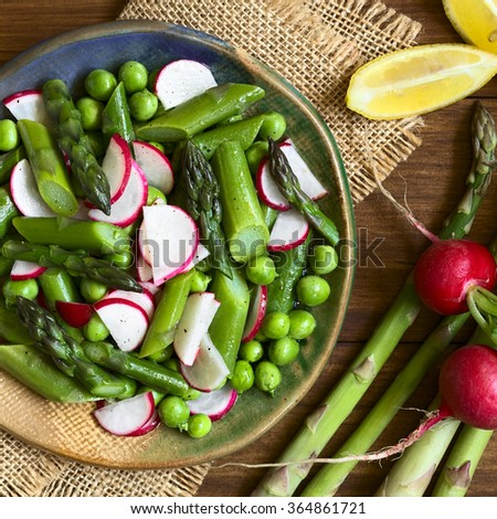 Fresh green asparagus, radish and pea salad served on plate, ingredients on the side, photographed overhead with natural light   - stock photo