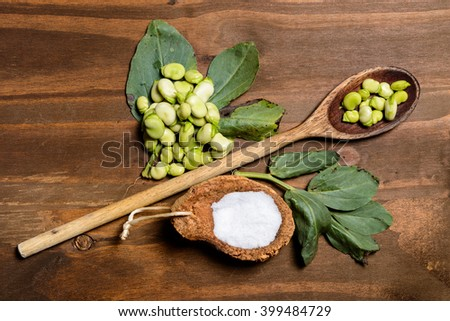 Fresh green beans seen from above on a rough wood floor brown color. Seasonings of Mediterranean cuisine: olive oil, salt. / Fresh broad beans in Flat lay. - stock photo