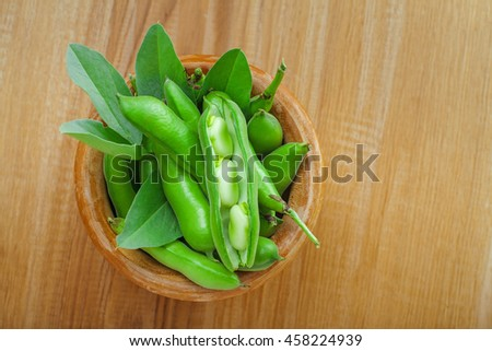 Fresh green broad beans in a bowl. Fresh raw vegetables on a wooden table. Ingredients healthy vegetarian food.