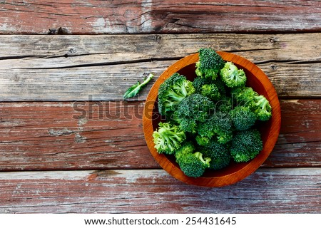Fresh green broccoli in wood bowl over rustic wooden background - healthy or vegetarian food concept  Top view. - stock photo