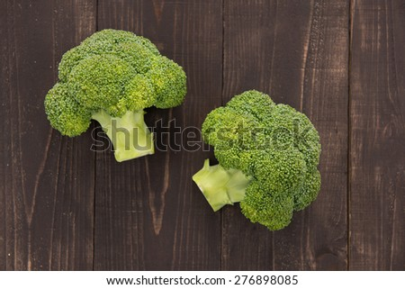 Fresh green broccoli on the wooden background. - stock photo