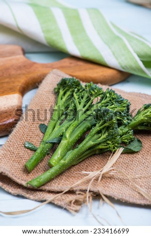 fresh green broccolini on wooden table - stock photo