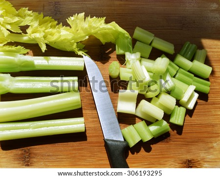 Fresh green celery stems on wooden cutting board, closeup - stock photo