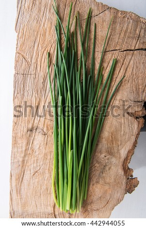 Fresh green chives on wooden board - stock photo
