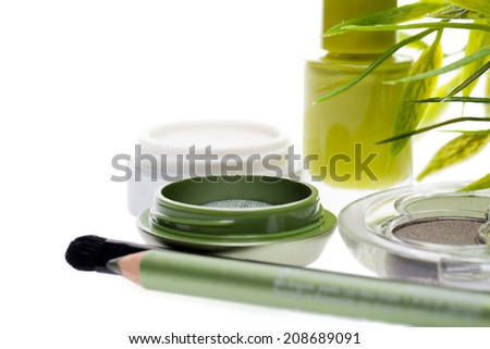 Fresh green cosmetics set with bamboo leaves with an eye pencil, eye shadow and nail varnish in a natural shade of green in a beauty and glamour concept, on white with copy space - stock photo