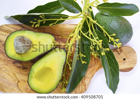 Fresh green cutted avocados with leaves on olive wood cutting board
