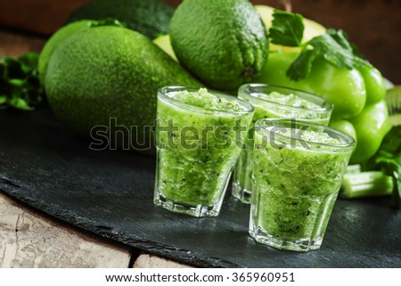 Fresh green detox smoothie made from apples, avocados, greens, lime and celery on a dark background, selective focus