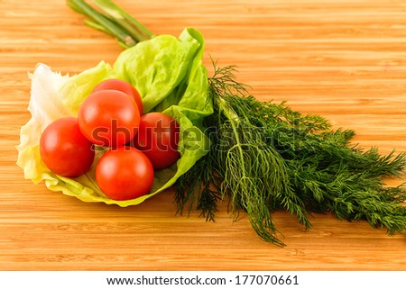 fresh green dill and tomatoes on wooden boards - stock photo
