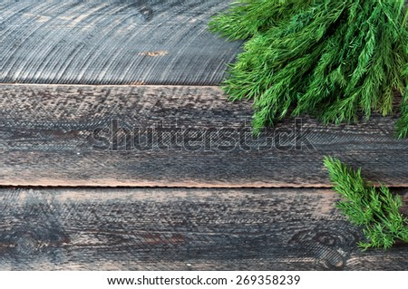 Fresh green dill on old wooden background - stock photo