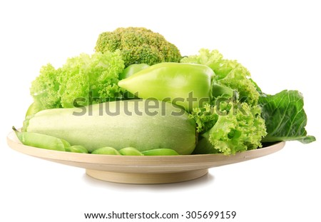 Fresh green food in wooden plate isolated on white - stock photo