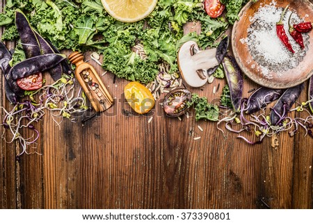 Fresh green kale and vegetables ingredients for cooking on rustic wooden background, top view, border. - stock photo