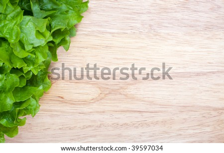 Fresh green lettuce on wooden board with space for text - stock photo
