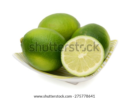 fresh green limes on plate isolated on white  - stock photo