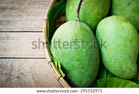 Fresh green mango on wooden table, Tropical fruit - stock photo
