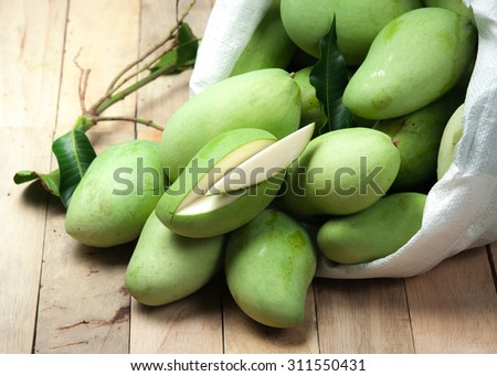 Fresh green mango with white plastic sack on wood - stock photo