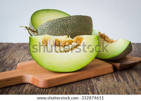 Fresh green melons sliced on wooden table over white background - stock photo