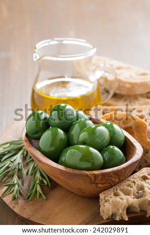 fresh green olives, olive oil and ciabatta on wooden board, vertical - stock photo