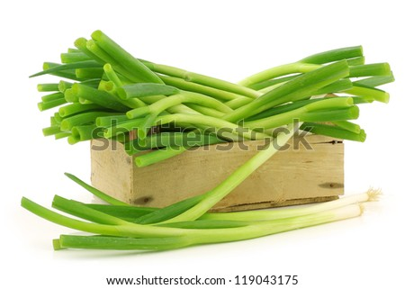 fresh green onions in a wooden crate on a white background - stock photo