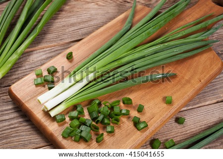 Fresh green onions on a cutting board.  - stock photo