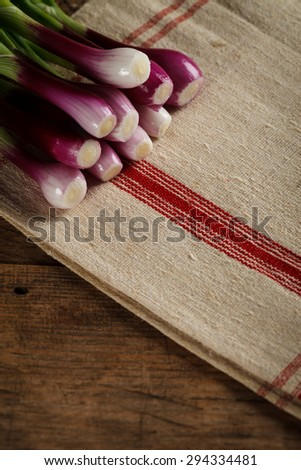 Fresh green onions on rustic woven tablecloth, wooden background - stock photo