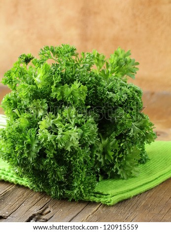 Fresh green, organic parsley on wooden table - stock photo
