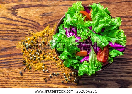 Fresh green organic salade on wooden background. Spices are scattered near - stock photo